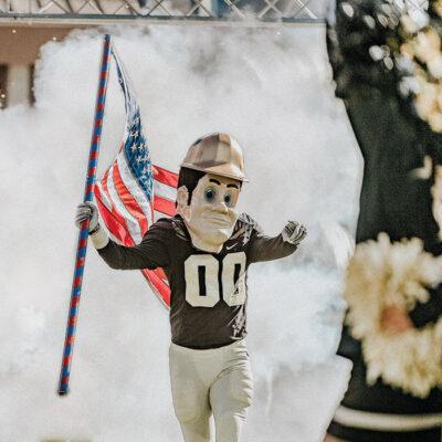 purdue pete running onto the football field waving an american flag