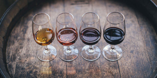 four wine glasses on a barrel